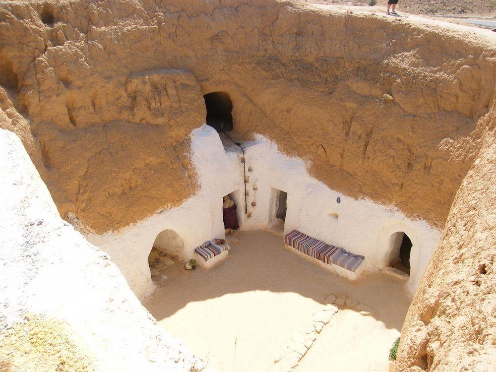 Zdjęcie wiosek wydrązonych w piaskowcach. Widać kilka wejść do tuneli, które prowadza do poszczegolnych pomieszczen.