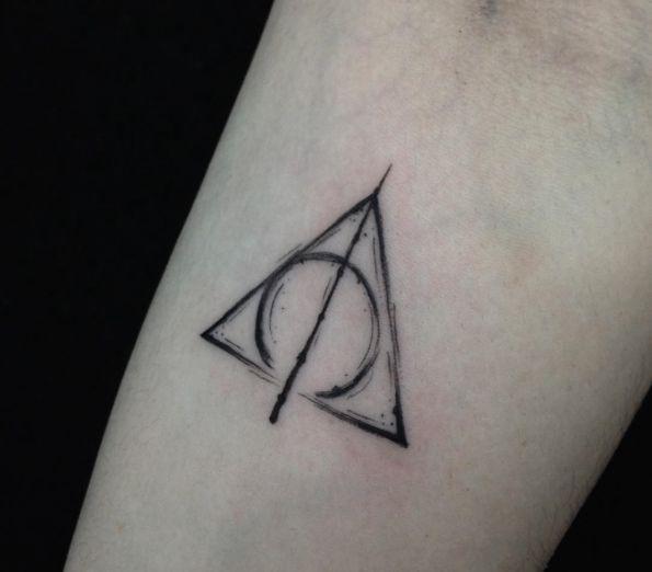 Minimalistyczny tatuaż przedstawiający Insygnia Śmierci