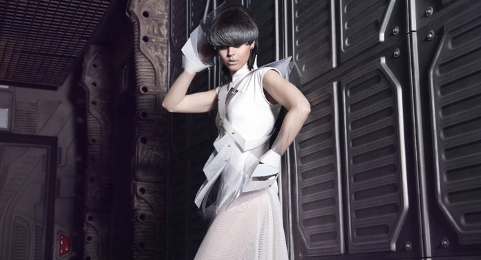 Kobieta ubrana w białą sukienkę z futurystycznymi elementami z fryzurą zakrywającą oczy