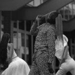 Czarno-białe zdjęcie mężczyzny tańczącego wśród dziewczyn ubranych na biało