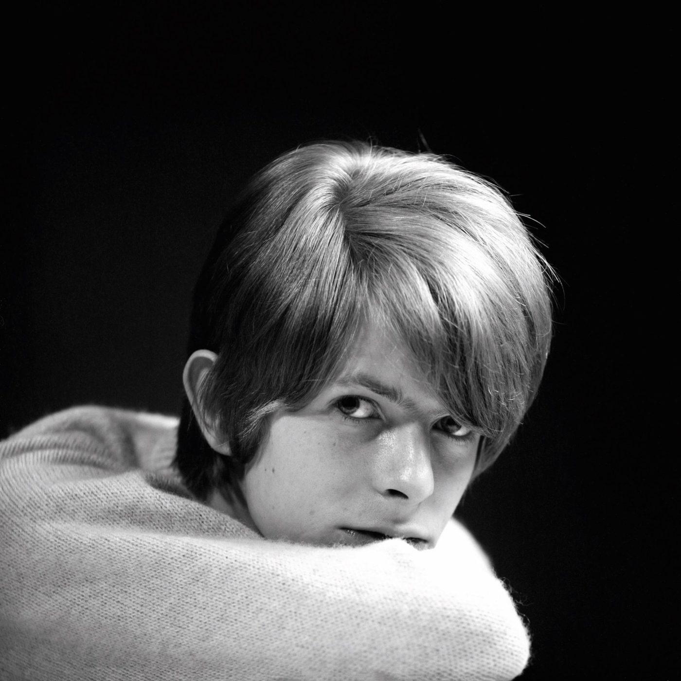 Czarno-biała fotografia blondwłosego mężczyzny opartego na swoim przedramieniu, ubranego w biały sweter