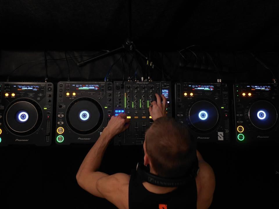 DJ Krzyku w koszulce na naramkach za deckami