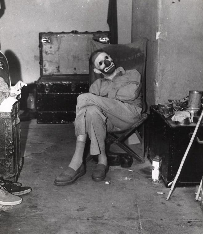 Klaun siedzi w zniszczonym pokoju.