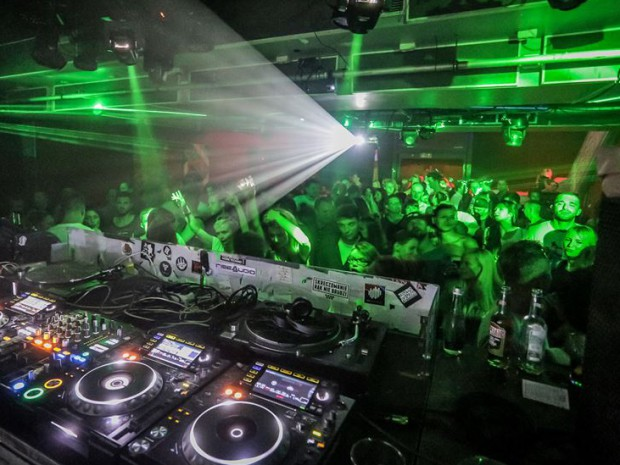 Oświetlona na zielono scena przed konsoletą DJ-a