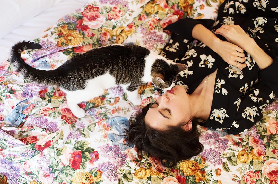 Brunetka leżaca na ziemi, nad nią stojący kot z pyszczkiem przy jej ustach