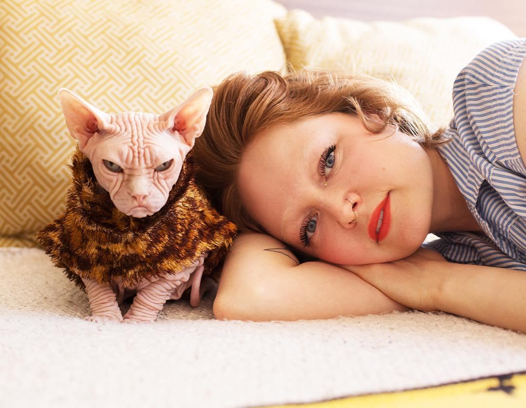 Kobieta leżaca na kanapie, obok niej kot bez futra