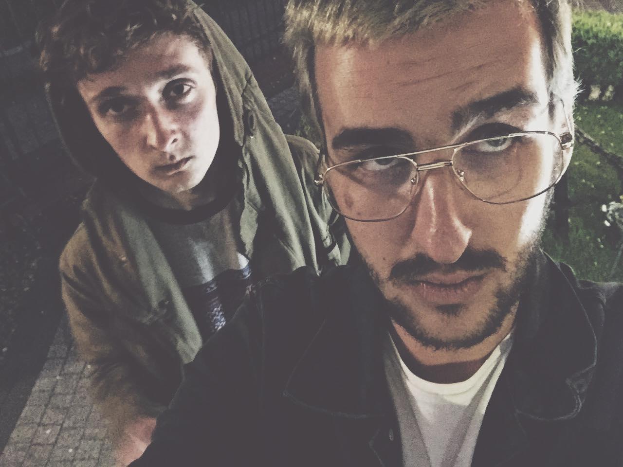 Dwóch mężczyzn stojących jeden za drugim, z któych jeden ma okulary, a drugi jest w kapturze