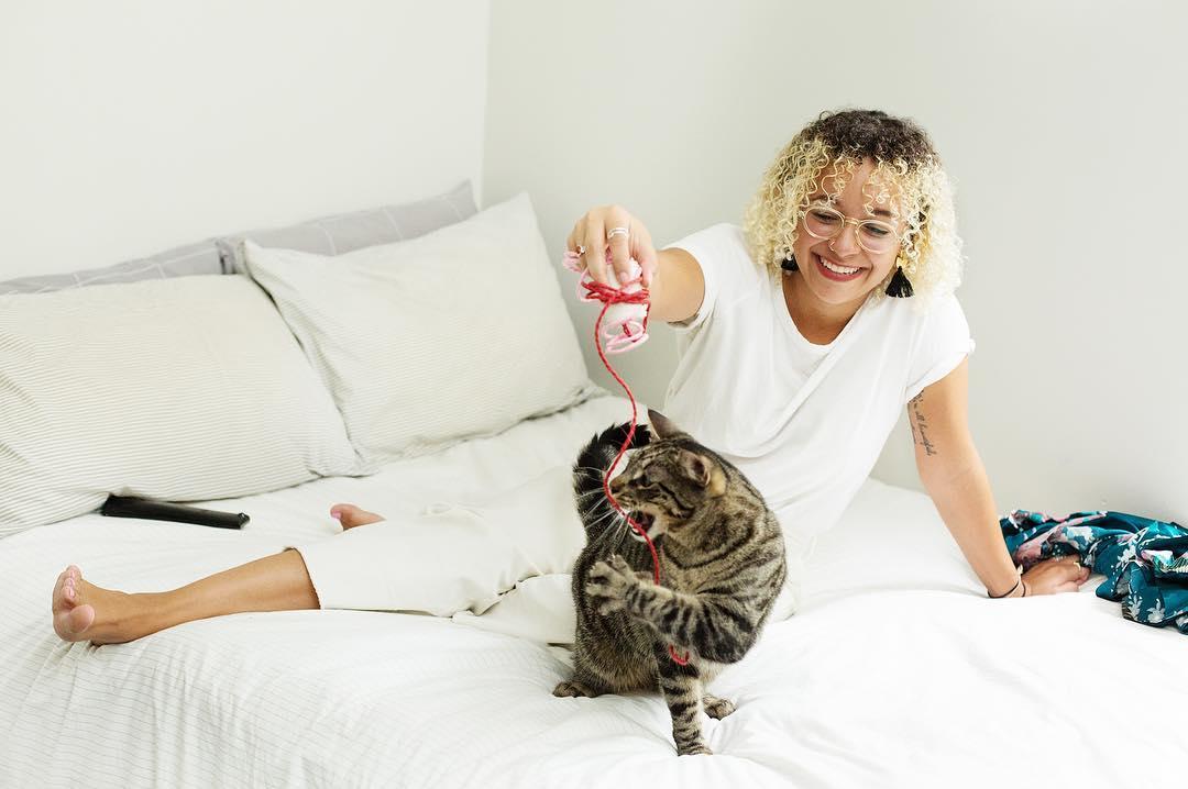 Kobieta ubrana na biało bawiąca sie z kotem na łóżku