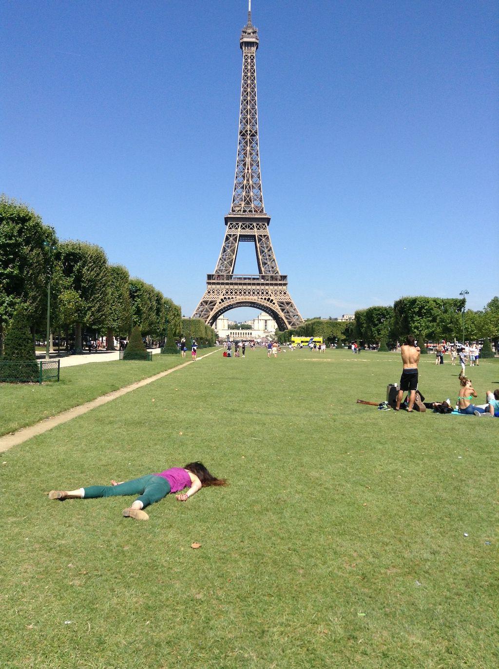 Dziewczyna leżąca twarzą do ziemi obok wieży Eiffle'a