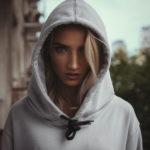 Dziewczyna w szarej bluzie z kapturem naciągniętym na głowę