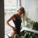 Dziewczyna w czarnym kostiumie kąpielowym stojąca w oknie w mieszkaniu