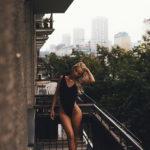 Blondynka w czarnym kostiumie kąpielowym stojąca na balkonie