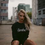 Blondynka siedząca na schodach w czarnej bluzie z napisem Wannabe