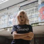 Blondynka w czarnej koszulce z napisem WANNABE na tle Graffiti