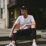 Chłopak w czarnych spodniach z dziurami, białej koszulce i czapce z daszkiem siedzacy na schodach
