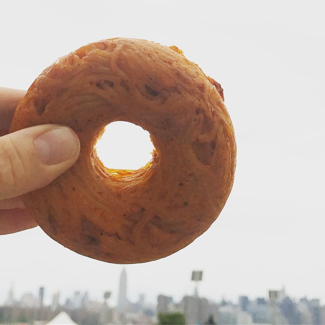 Donut trzymany w palcach na tle nieba