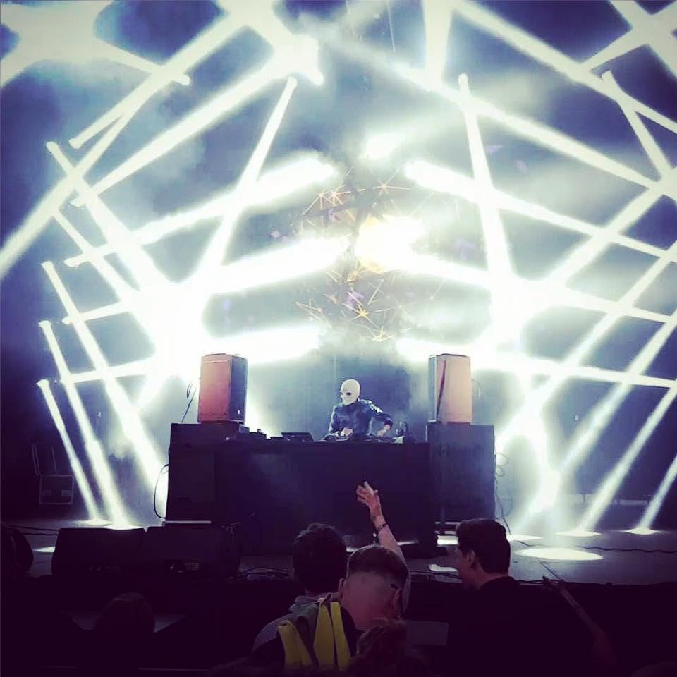 DJ w masce stojący na scenie za deckami