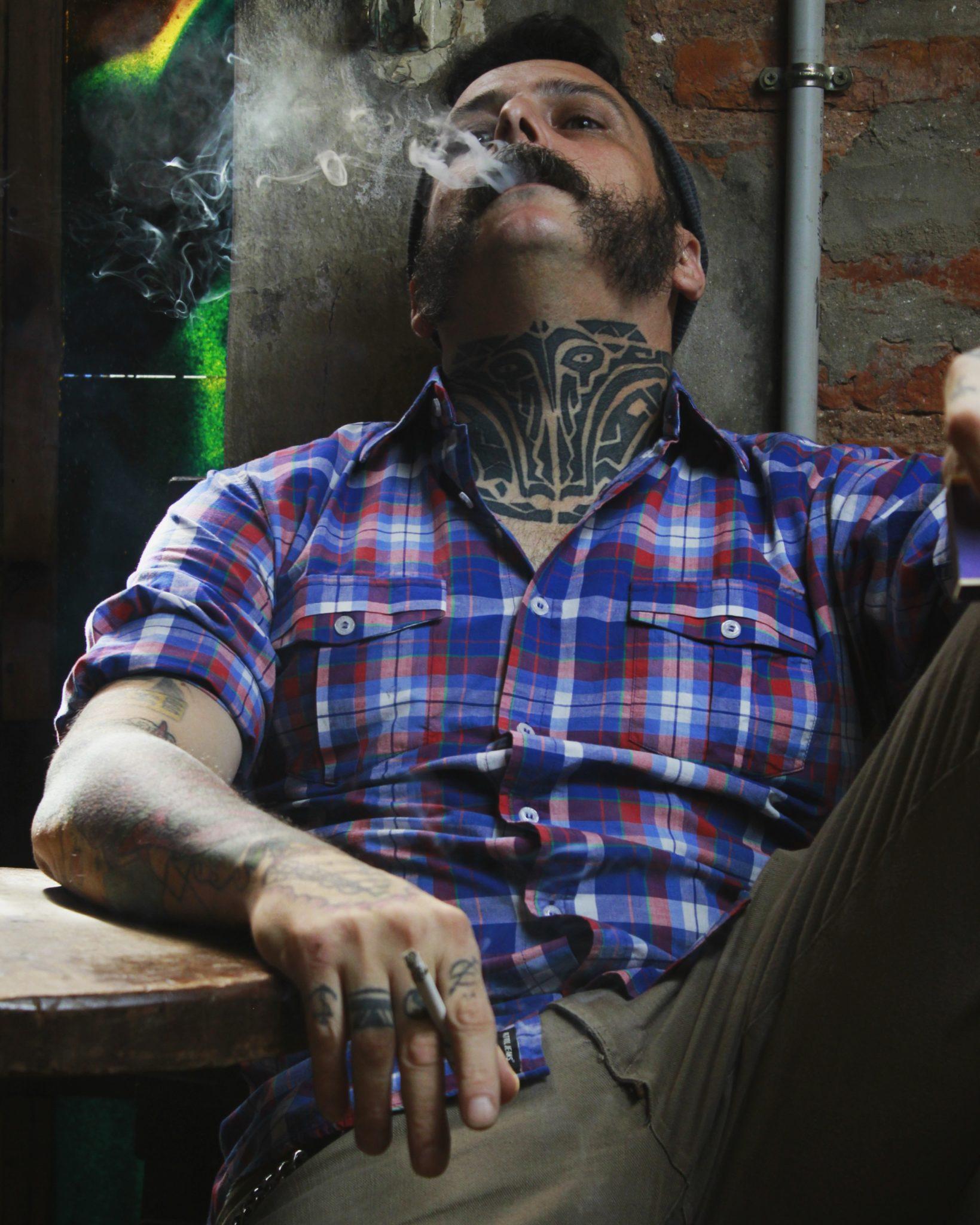 Gość w koszuli, palący papierosa i siedzący na fotelu