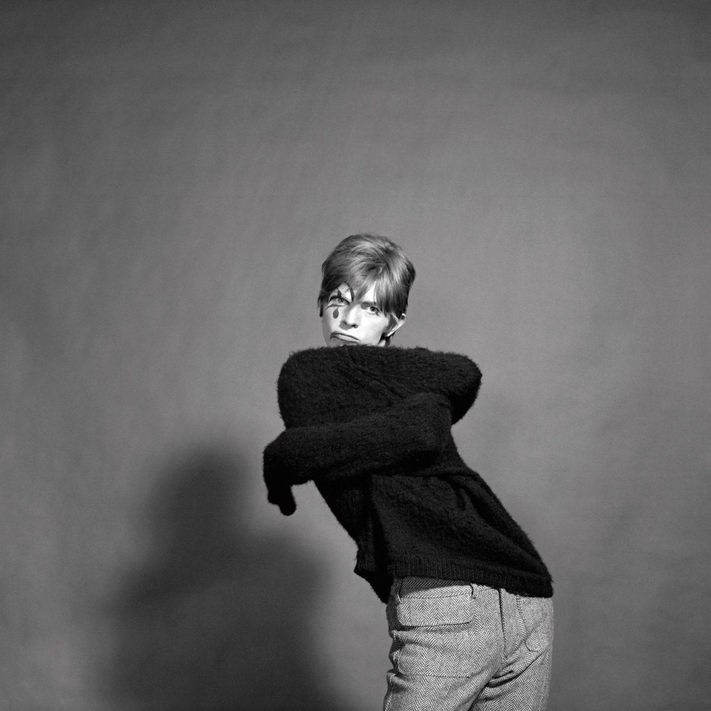 Czarno-białe zdjęcie wygiętego mężczyzny obejmujące się swoimi ramionami, w czarnym swetrze
