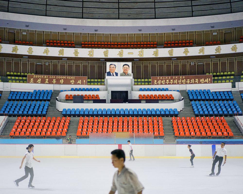 Widok na wnętrze zadaszonego lodowiska, w tle widać obrazy przywódców Korei