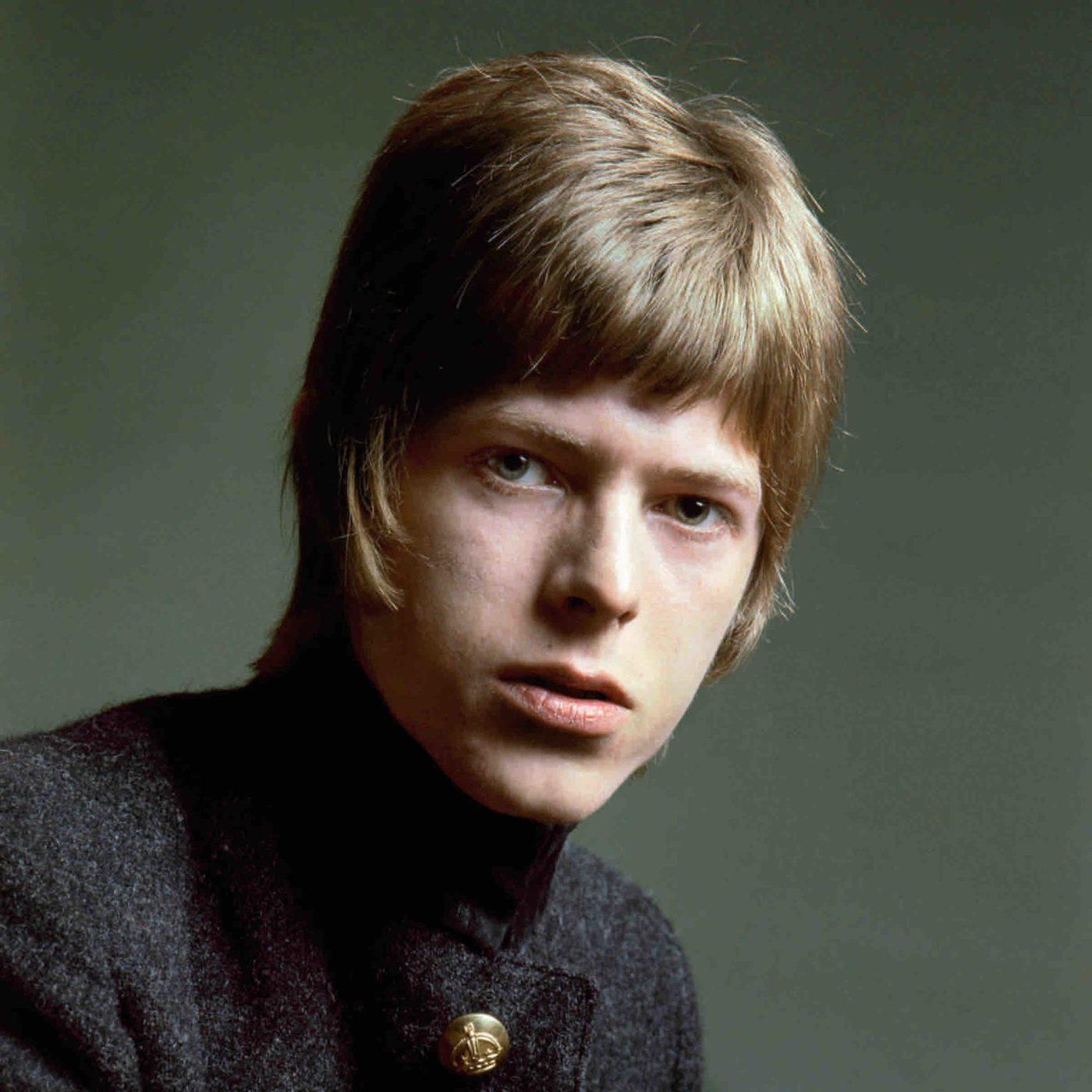 Mężczyzna z dłuższymi blond włosami w ciemnym swetrze