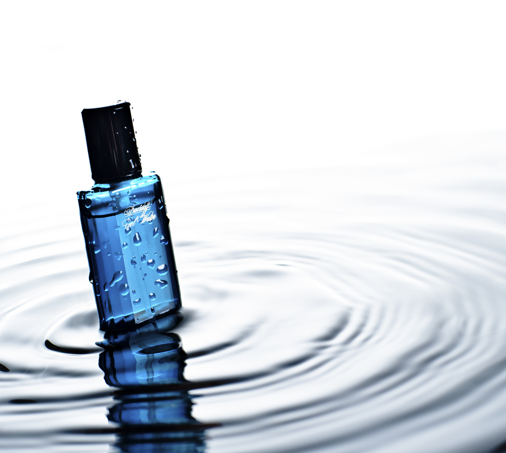Niebieska butelka perfum zanurzona w wodzie