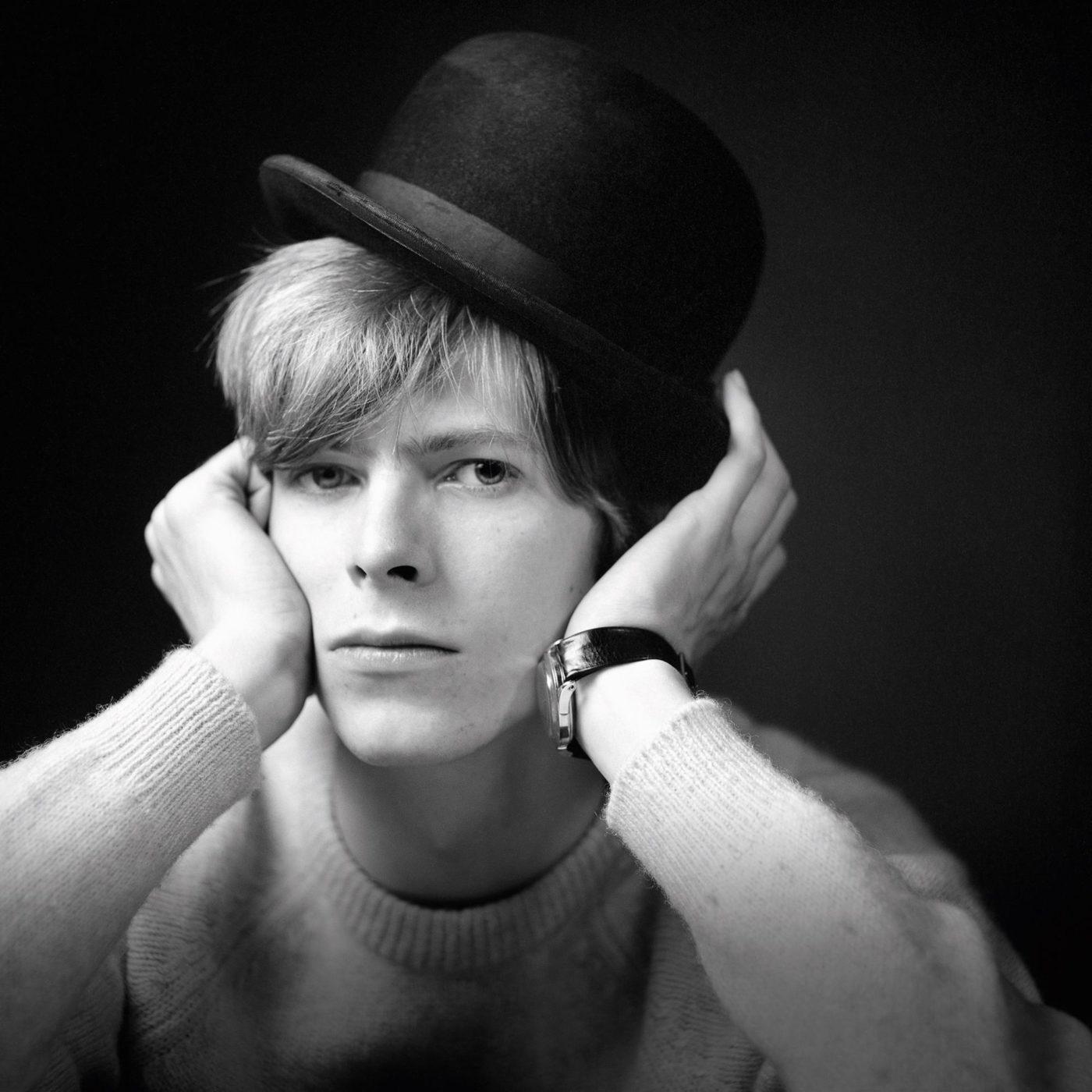 Czarno-białe zdjęcie mężczyzny w czarnym kapeluszu z dłońmi na twarzy