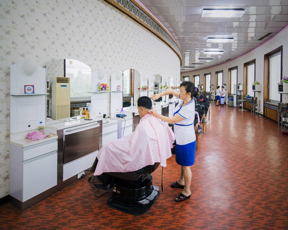 Widok wnętrza salonu fryzjerskiego, na krześle siedzi mężczyzna i strzyże go kobieta