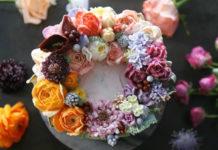Biały tort leżący na ciemnym stole udekorowany realistyczne wyglądającymi kwiatami