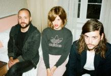 Łysy chłopak z bródką, dziewczyna w krótkich, gęstych włosach w bluzie Addidas i chłopak z dłuższymi brązowymi włosami siedza na łóżku