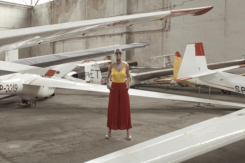 Kobieta ubrana w czerwoną spódnicę i żółtą bluzkę stojąca w otoczeniu samolotów
