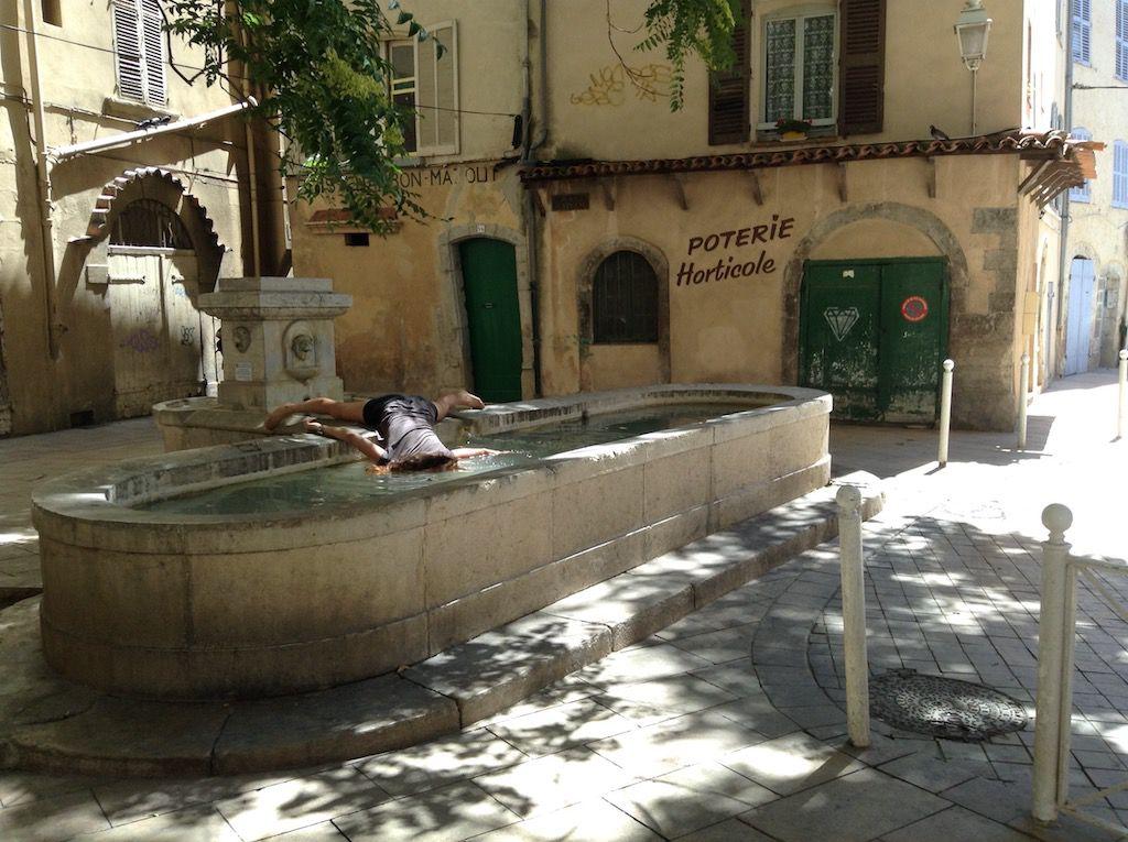 Dziewczyna leżąca z głową w zabytkowej fontannie