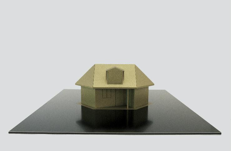 Szare tło z kartonowym domkiem na czarnej podstawie