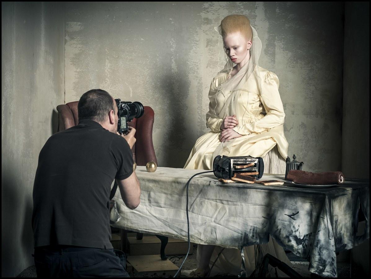 Albinoska w białej sukni pozuje fotografowi.