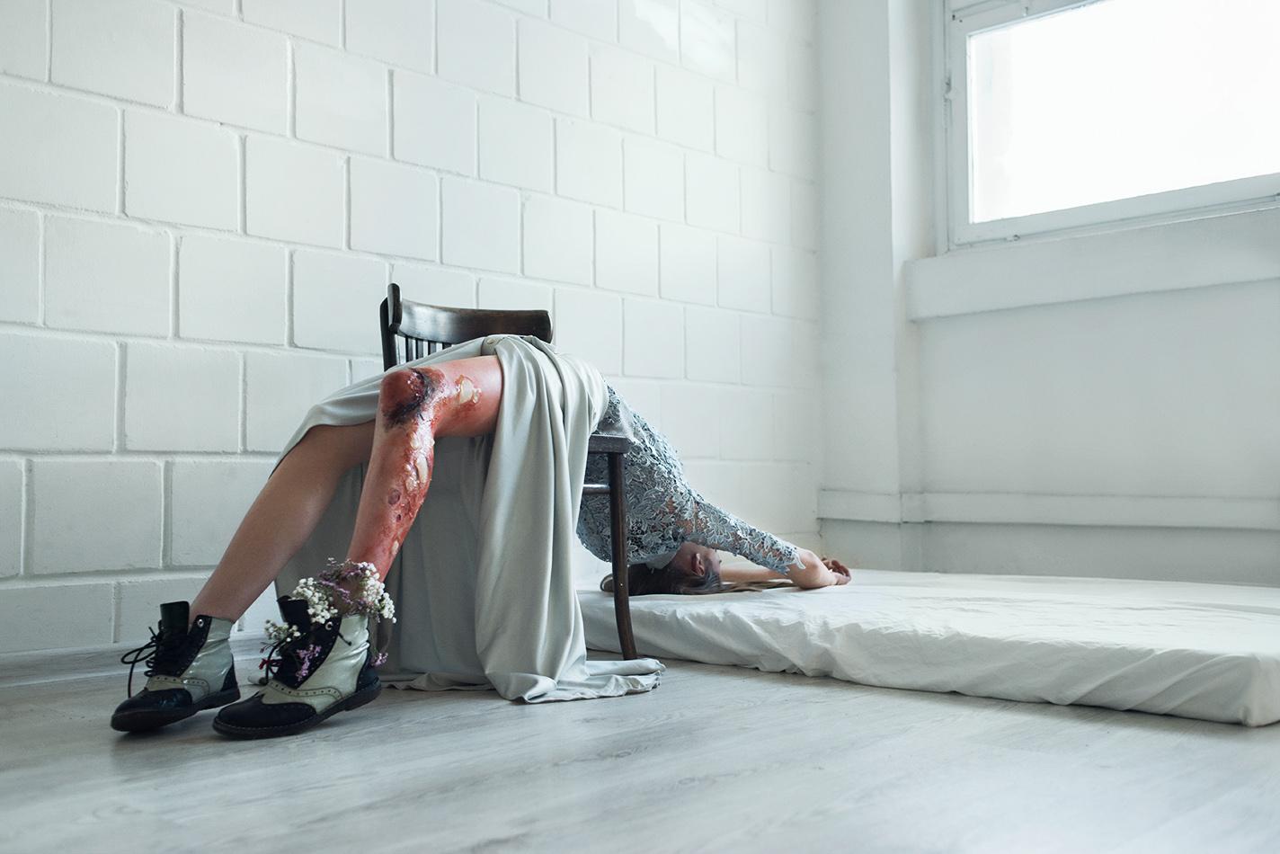 Zwisająca z krzesła kobieta z zakrwawioną nogą