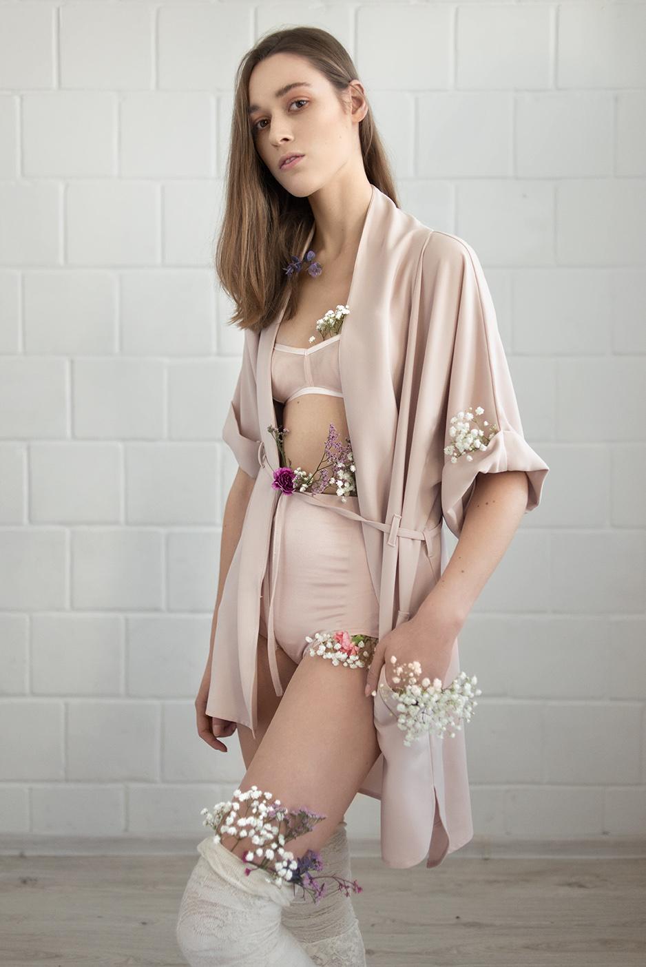 Dziewczyna od szyi w dół ubrana w satynową, brudno-różową bieliznę i szlafrok