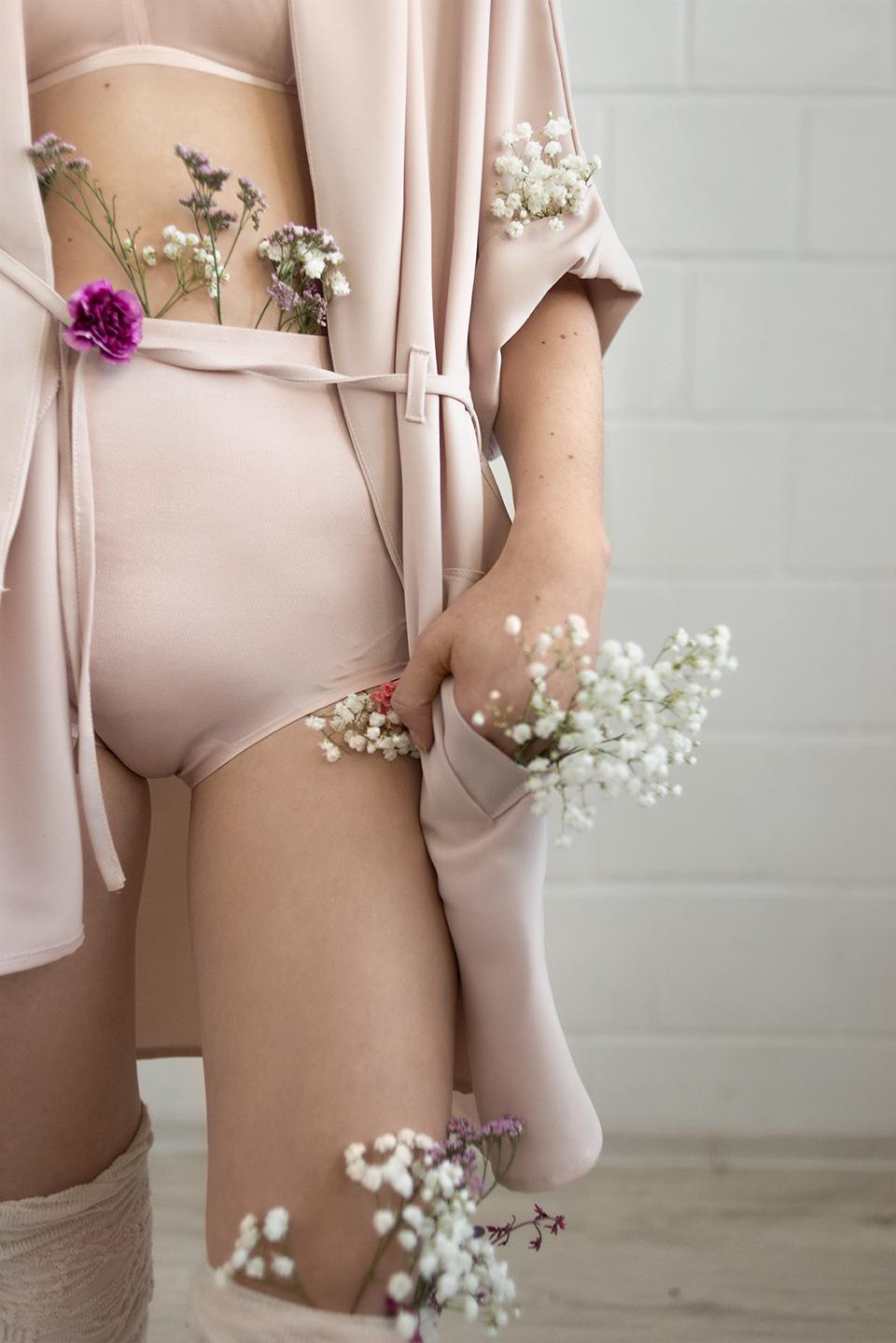 Kobieta od pasa do kolona ubrana w brudno-różową bieliznę, z kwiatami w dłoniach i za linią majtek