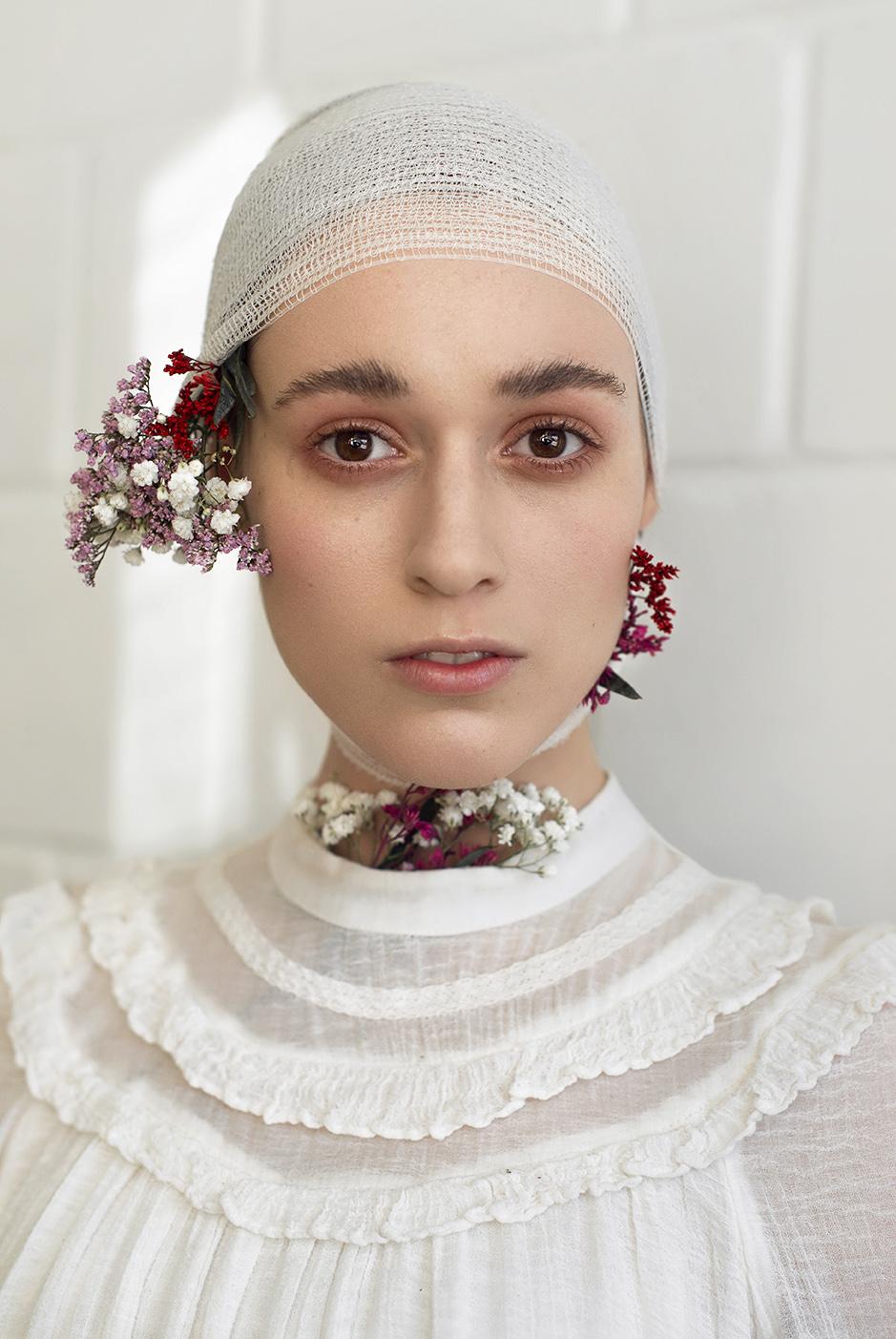 Dziewczyna ubrana cała na biało, w bluzkę pod szyję z koronką, białą chustą na głowie i wplecionymi kwiatami