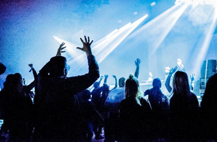 Tłum stojący przy scenie oświetlonej niebieskim światłem