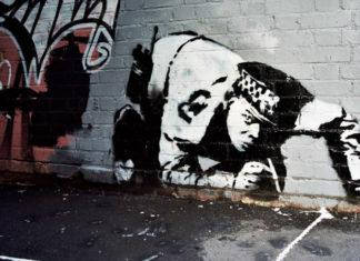 Mural przedstawiający policjanta wciągającego kreskę kokainy z chodnika