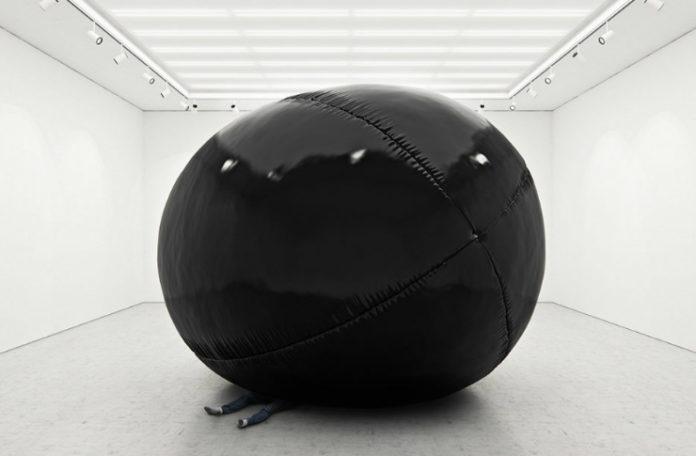 Duży czarny balon w białym pomieszczeniu przygniatający człowieka.