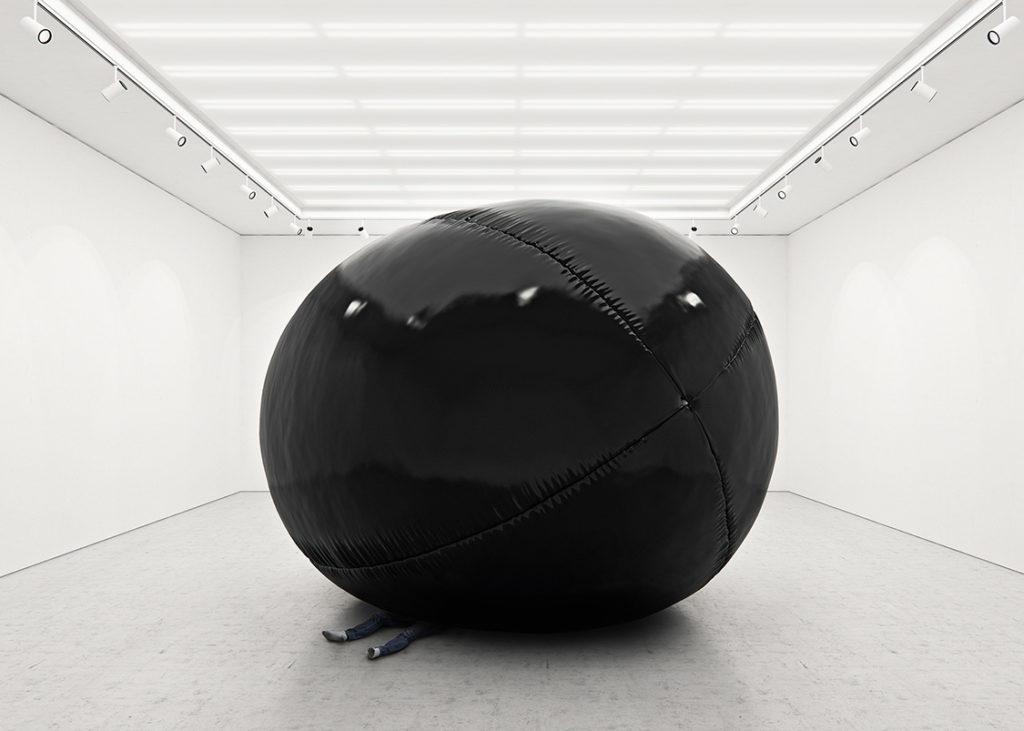 Duży czarny balon w białym pomieszczeniu, który przygniata człowieka.