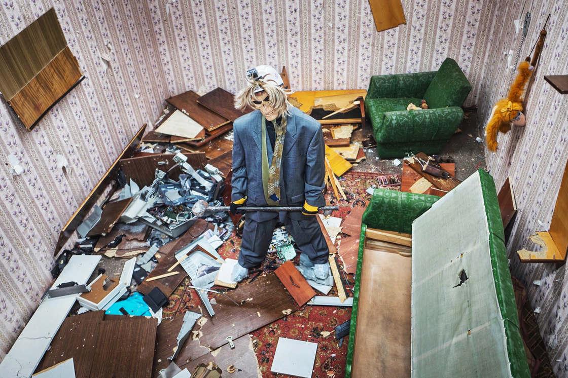 Człowiek w masce z młotem stoi w mieszkaniu na totalnym pobojowisku