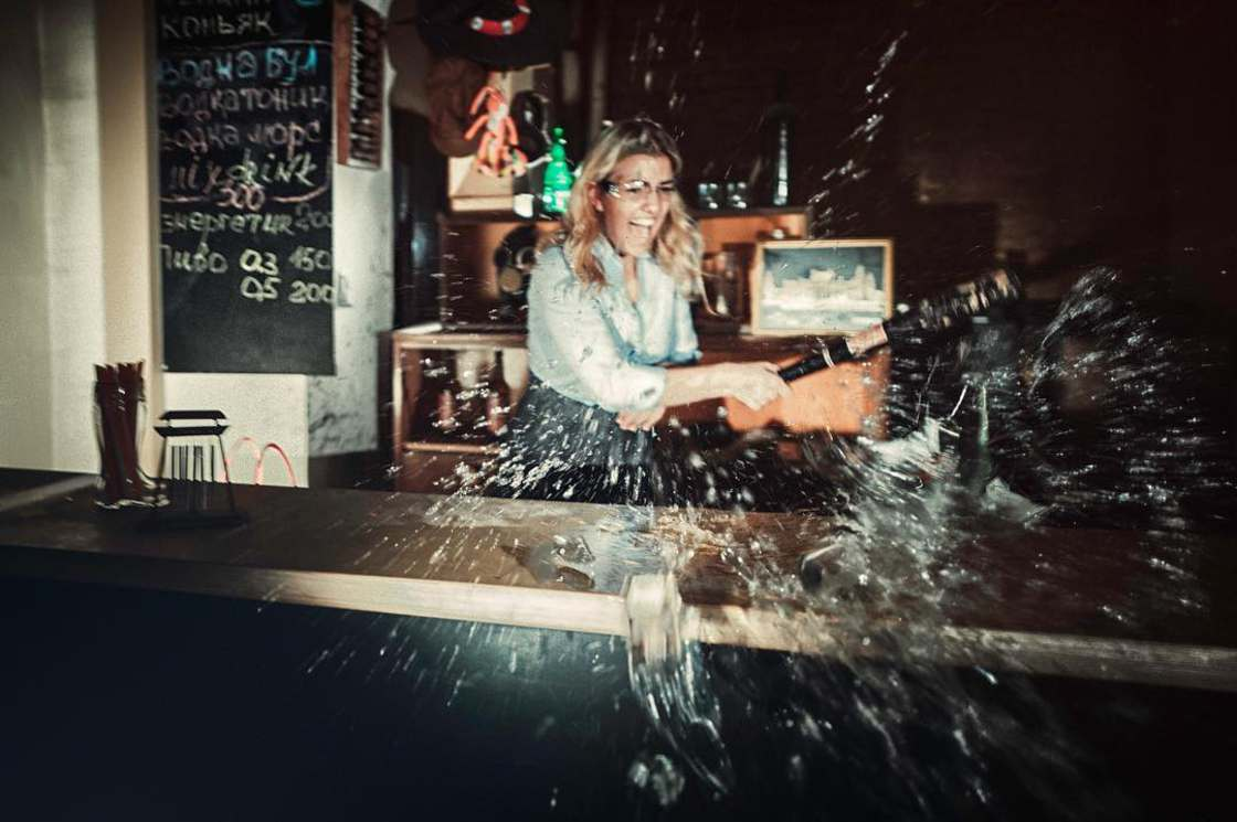 Kobieta rozbija szklane wyposażenie baru