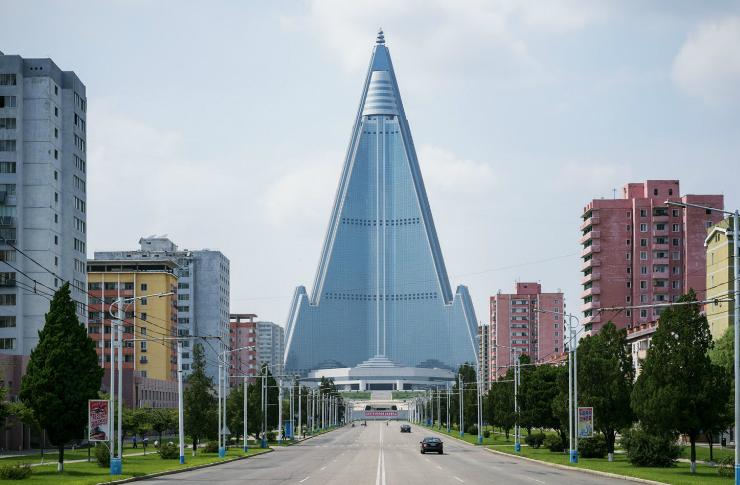 Droga. Po bokach bloki. Na końcu drogi wieżowiec w kształcie ostrosłupa.
