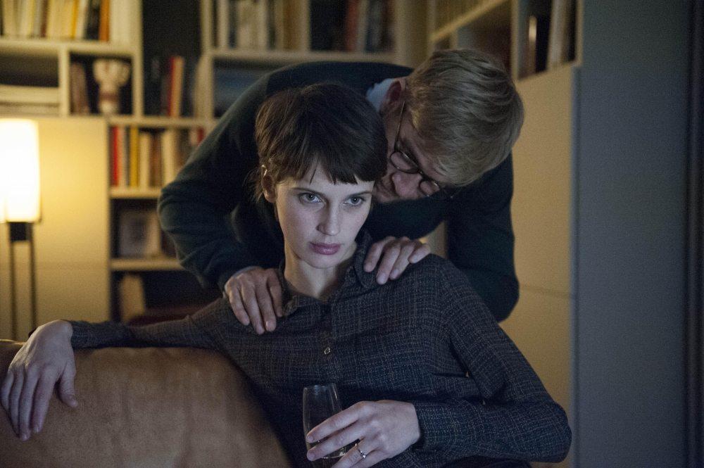 Kobieta siedzi na kanapie, a nad nią pochyla się mężczyzna w okularach