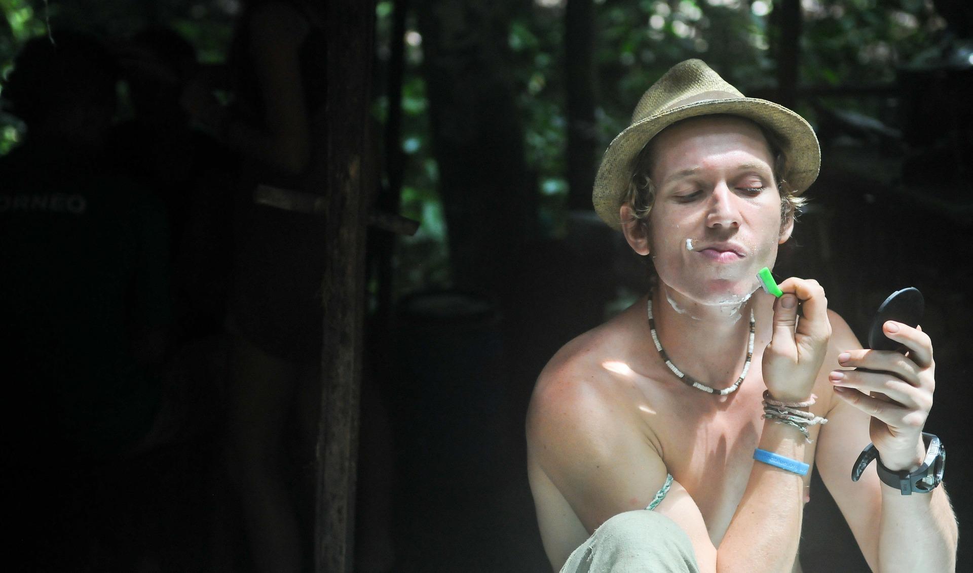 Mężczyzna w słomkowym kapeluszu, któy się goli