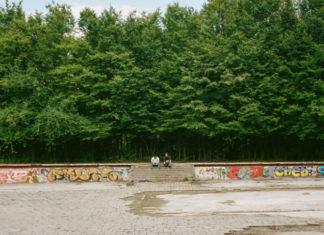 Widok na zielony las, beton i dwóch chłopaków w oddali