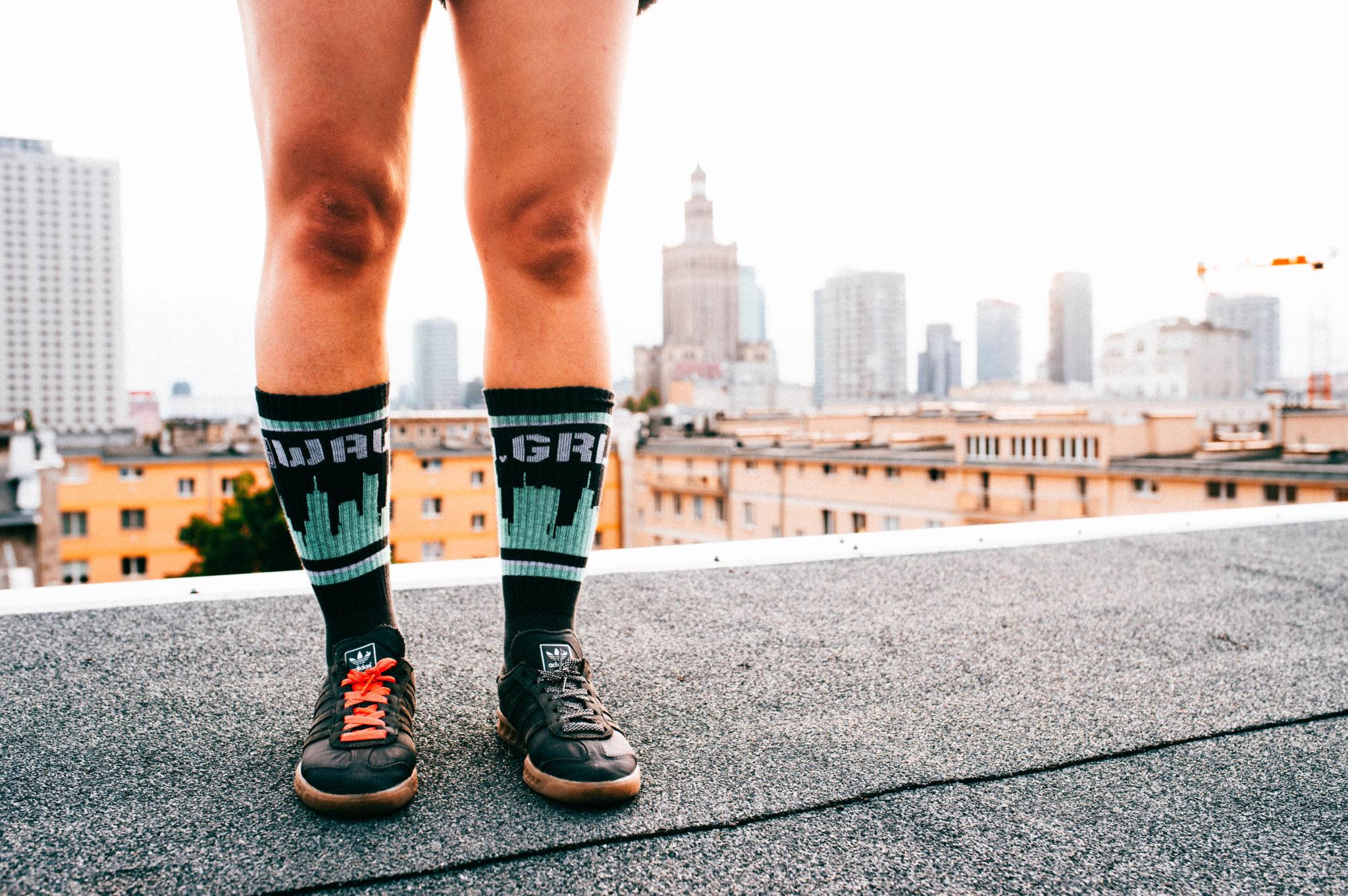 Męskie nogi w addidasach, ubrane w skarpetki z motywem Warszawy
