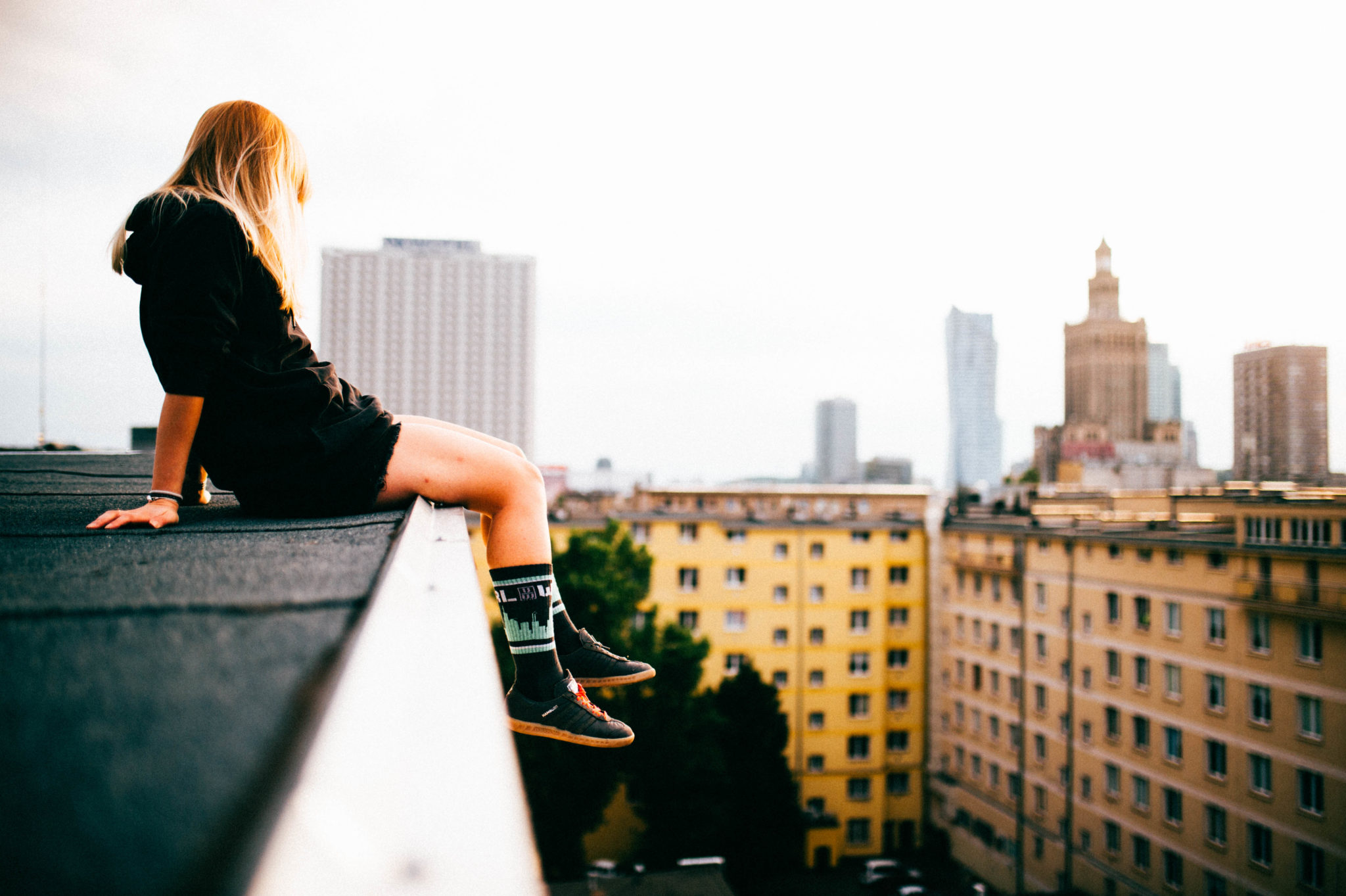 Dziewczyn siedząca na krawędzi budynku